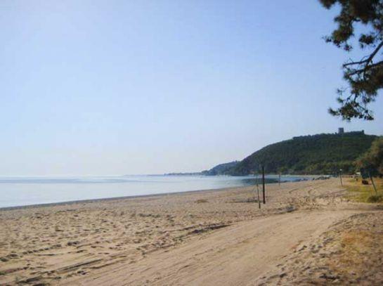 Песчаный пляж на берегу Эгейского моря. Вдали видна крепость Платамон